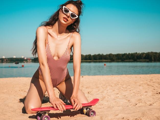 Jovem mulher bonita em trajes de banho e óculos de sol posando na praia