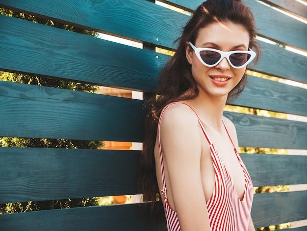 Jovem mulher bonita em trajes de banho e óculos de sol posando na rua