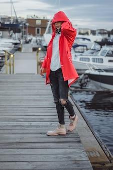 Jovem mulher bonita em um casaco vermelho no porto do iate. estocolmo, suécia