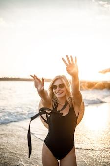 Jovem mulher bonita em um maiô preto e um chapéu com óculos caminha ao longo da praia na turquia ao pôr do sol. o conceito de recreação marítima. foco seletivo