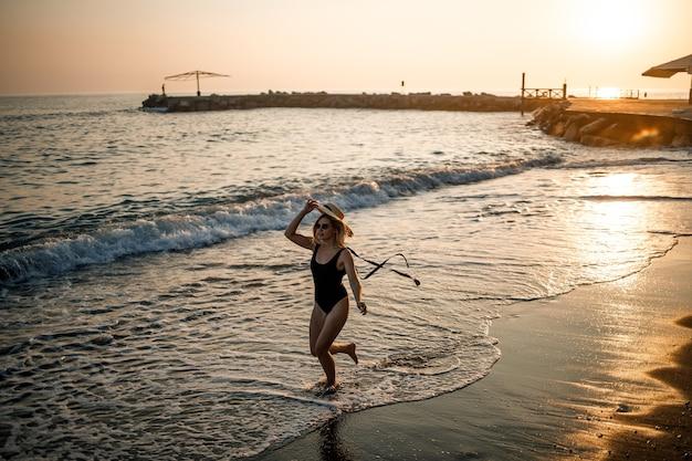 Jovem mulher bonita em um maiô preto e um chapéu com óculos caminha na praia ao pôr do sol. o conceito de recreação marítima. foco seletivo