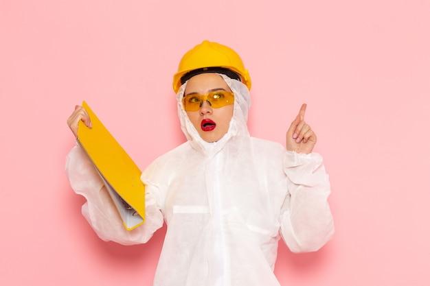 Jovem mulher bonita em um terno branco especial e capacete amarelo segurando limas amarelas na rosa