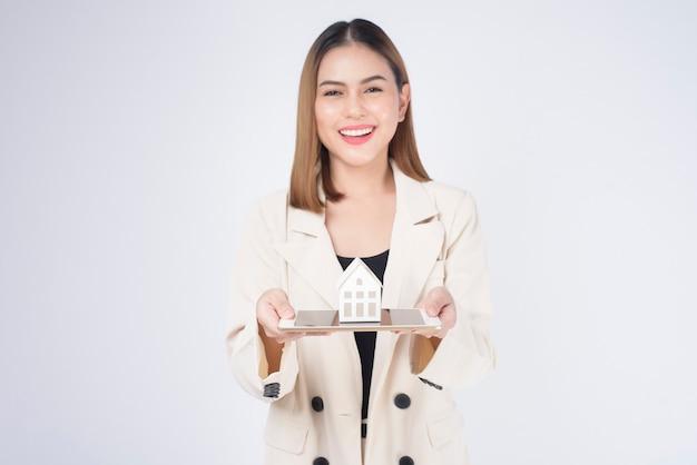 Jovem mulher bonita em um terno segurando uma pequena casa modelo sobre um estúdio de fundo branco