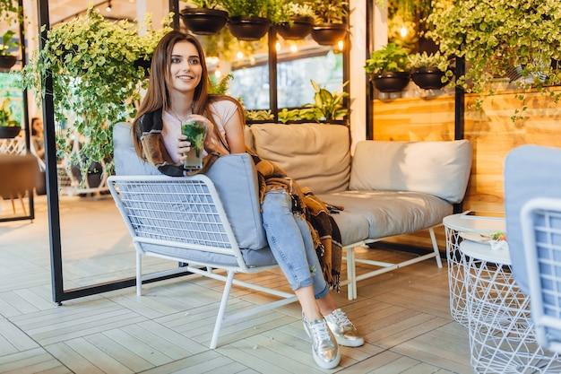 Jovem mulher bonita em um terraço de verão com roupas casuais está bebendo um coquetel. coberto com um cobertor