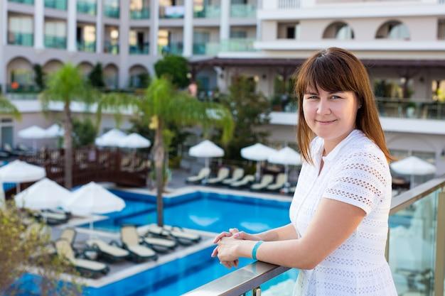 Jovem mulher bonita em um vestido branco posando na varanda de um hotel moderno