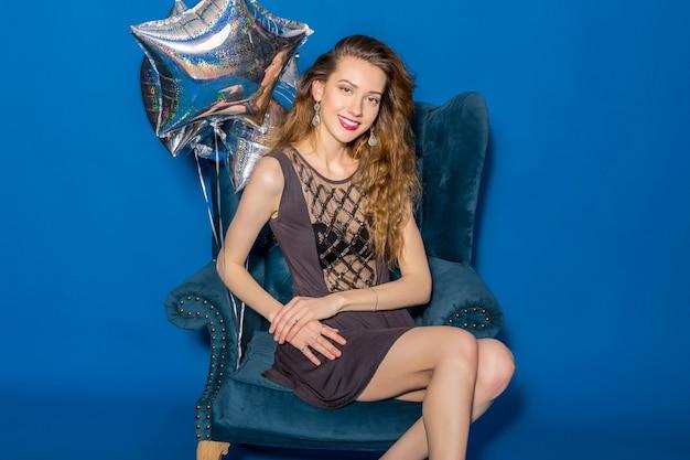 Jovem mulher bonita em um vestido cinza sentada em uma poltrona azul com balões prateados
