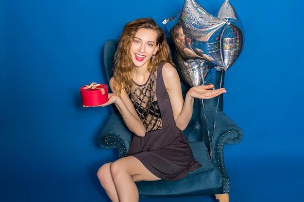 Jovem mulher bonita em um vestido cinza sentada em uma poltrona azul segurando uma caixa de presente