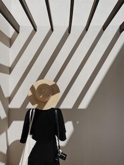 Jovem mulher bonita em um vestido preto, chapéu de palha e câmera fotográfica retrô perto de uma parede branca com sombras da luz do sol do trilho