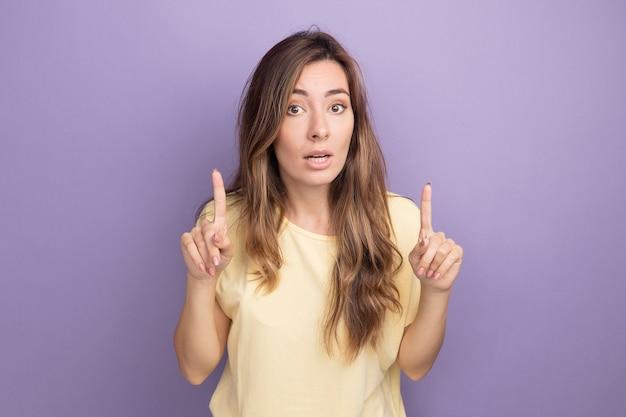 Jovem mulher bonita em uma camiseta bege olhando para a câmera com uma expressão confiante no rosto inteligente