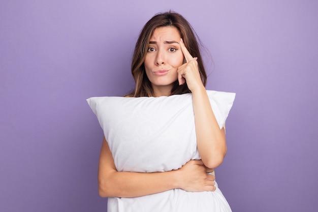 Jovem mulher bonita em uma camiseta bege segurando um travesseiro branco, olhando para a câmera, confusa e descontente, apontando para a têmpora