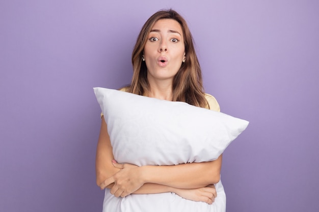 Jovem mulher bonita em uma camiseta bege segurando uma almofada branca olhando para a câmera surpresa em pé sobre o roxo