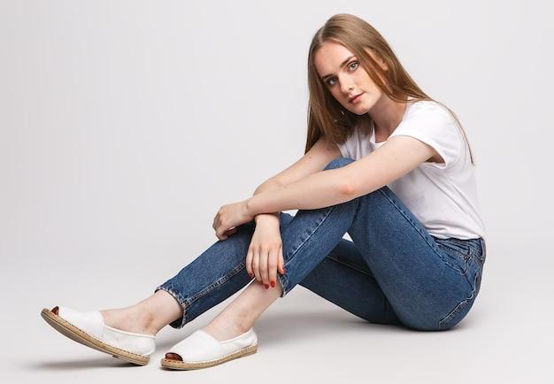 Jovem mulher bonita em uma camiseta branca e calça jeans branca