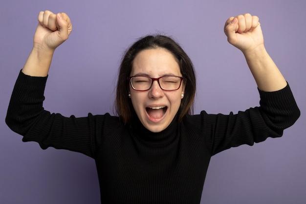 Jovem mulher bonita em uma gola preta e óculos levantando os punhos, feliz e animada em pé sobre a parede roxa