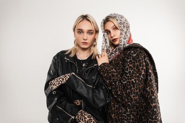 Jovem mulher bonita em uma jaqueta de couro preta e uma garota atraente em um casaco de pele elegante e glamouroso de leopardo em um lenço perto de uma parede vintage