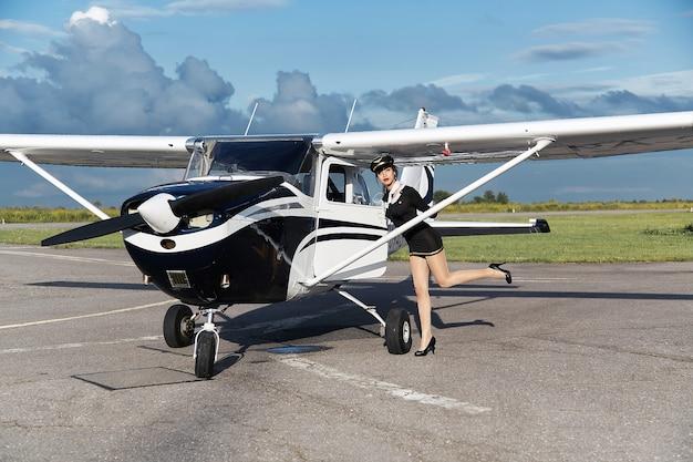 Jovem mulher bonita engraçada piloto ou aeromoça na frente do avião, estilo pin up