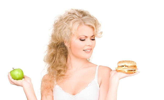 Jovem mulher bonita escolhendo entre hambúrguer e maçã