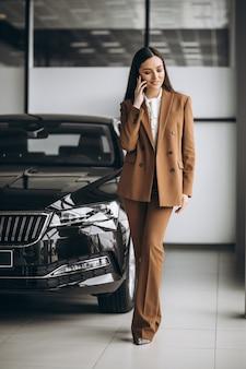 Jovem mulher bonita escolhendo o carro em uma sala de exposições