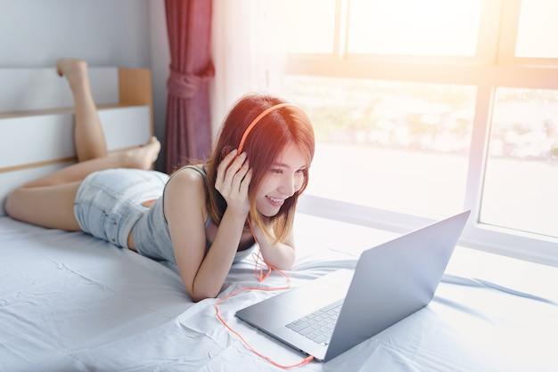 Jovem, mulher bonita, escutar música, em, fones, ligado, a, cama, ela, é, usando, laptop, com
