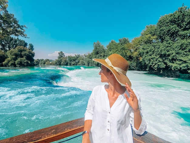 Jovem mulher bonita está de pé perto da cachoeira manavgat