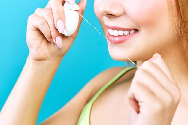 Jovem mulher bonita está envolvida na limpeza dos dentes