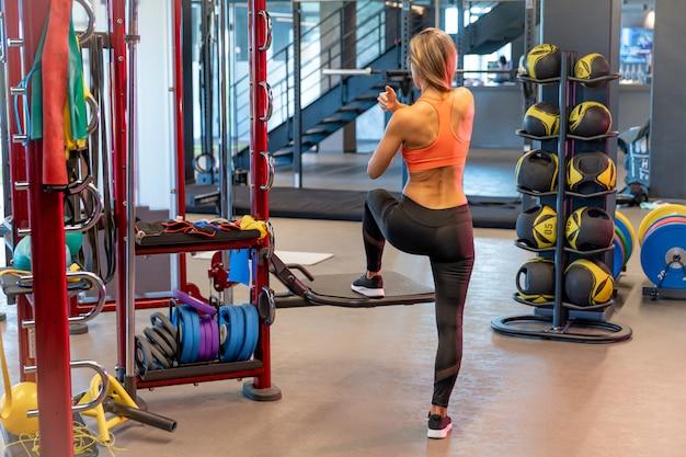 Jovem mulher bonita está esticando na academia antes do exercício