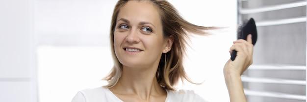 Jovem mulher bonita está olhando para seu reflexo no banheiro e penteando o cabelo. estilo de cabelo de mulher no conceito de casa.