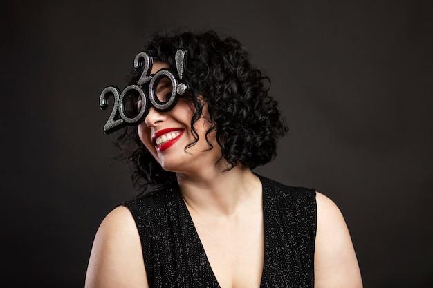 Jovem mulher bonita está rindo. morena com cabelos cacheados e lábios vermelhos. humor de ano novo festivo. fundo preto.