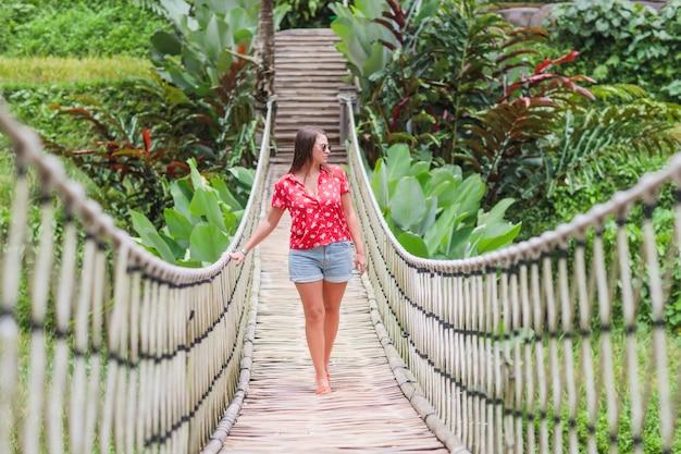 Jovem mulher bonita está sentada na ponte de suspensão na floresta tropical.