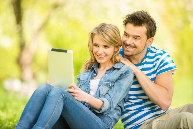 Jovem mulher bonita está sentado em madeira com tablet.