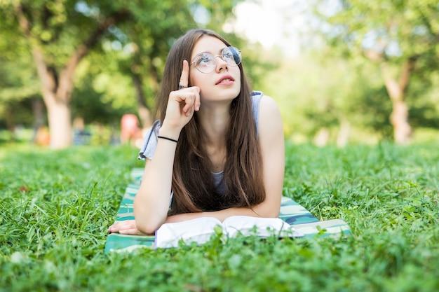 Jovem mulher bonita estabelece em campo verde e lê o livro.