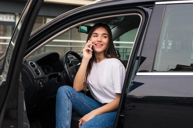 Jovem mulher bonita falando ao telefone, sentada no carro