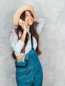 Jovem mulher bonita falando no telefone. menina chocada na moda em roupas de verão casual macacão e chapéu.