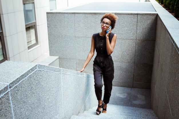 Jovem mulher bonita falando no telefone, subindo escadas