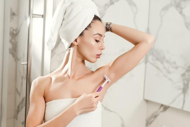 Jovem mulher bonita faz a barba axilas com uma navalha envolto em toalhas no banheiro