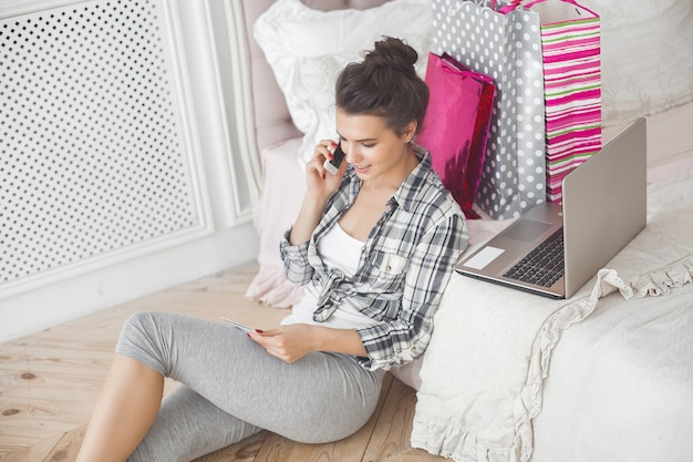 Jovem mulher bonita fazendo compras on-line em casa