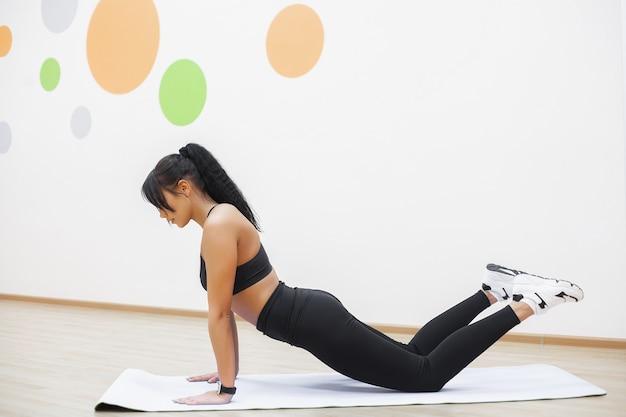Jovem mulher bonita fazendo flexões no ginásio. treino de garota fitness no ginásio
