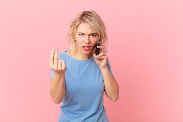 Jovem mulher bonita fazendo gesto de capice ou dinheiro, dizendo para você pagar. conceito de célula