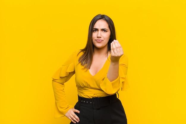 Jovem mulher bonita fazendo gesto de capice ou dinheiro, dizendo para você pagar suas dívidas! isolado contra parede laranja
