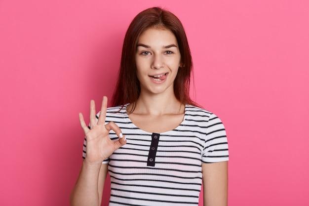 Jovem mulher bonita fazendo sinal de ok com os dedos e mostrando sua língua, com expressão engraçada, posando isolada sobre parede rosa.