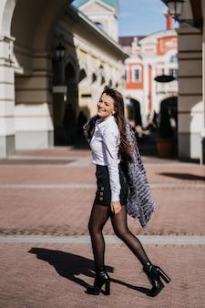 Jovem mulher bonita feliz com o casaco de pele, saia branca e camisa preta andando na cidade.
