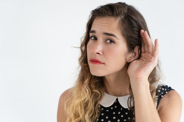 Jovem mulher bonita focalizada que guarda a mão perto da orelha e que olha a câmera.
