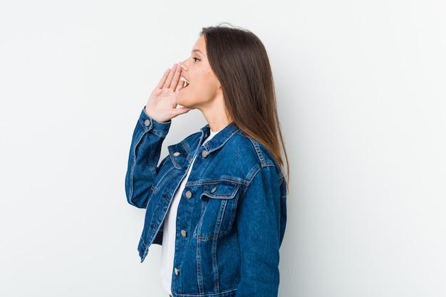 Jovem mulher bonita gritando e segurando a palma perto da boca aberta.