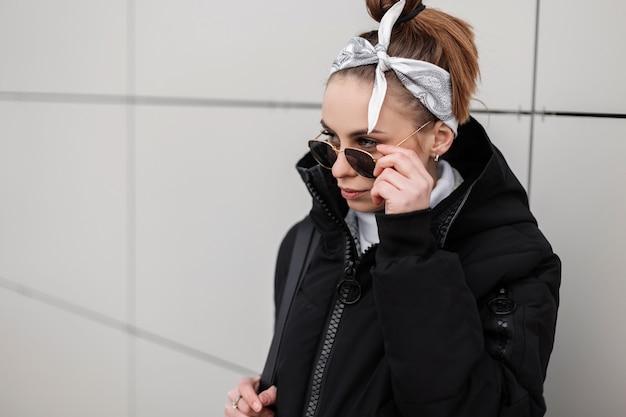 Jovem mulher bonita hippie com um penteado elegante com uma bandana elegante em óculos de sol pretos em uma jaqueta preta da moda posa perto da parede em um dia quente de inverno. garota americana dando um passeio.