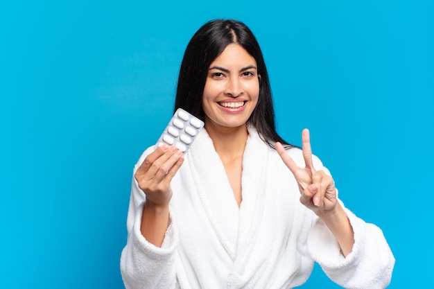 Jovem mulher bonita hispânica com comprimido de comprimidos. conceito de doença