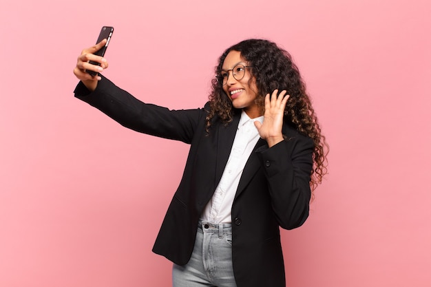 Jovem mulher bonita hispânica. negócios de expressão feliz e surpreso e conceito de smartphone