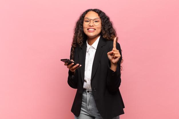 Jovem mulher bonita hispânica orgulhosa de expressão empresarial e conceito de smartphone