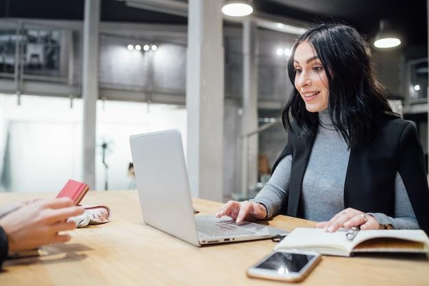 Jovem, mulher bonita, indoor, usando computador, sentando, trabalhando, escrivaninha