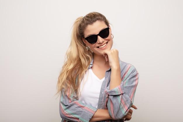 Jovem mulher bonita latina contra parede plana usando óculos de sol