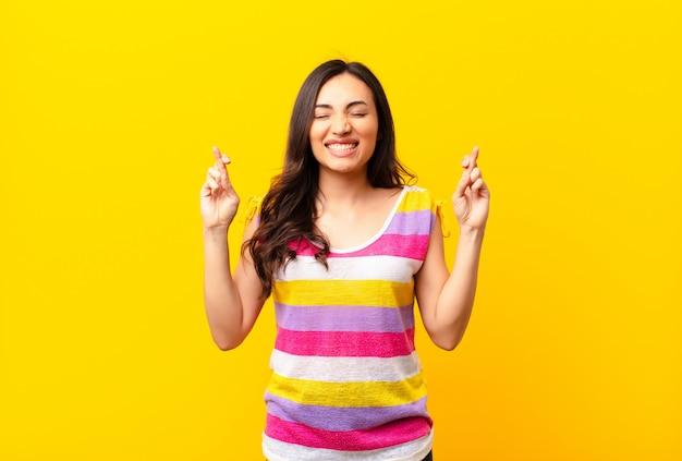 Jovem mulher bonita latina sorrindo e cruzando ansiosamente os dois dedos, sentindo-se preocupado e desejando ou esperando boa sorte contra a parede plana