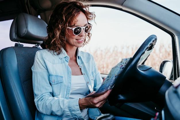 Jovem mulher bonita lendo um mapa em um carro. conceito de viagens